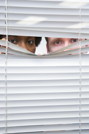 snooping: Colleagues looking through blinds Stock Photo