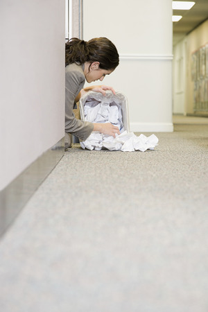 snooping: Woman searching in waste paper Stock Photo