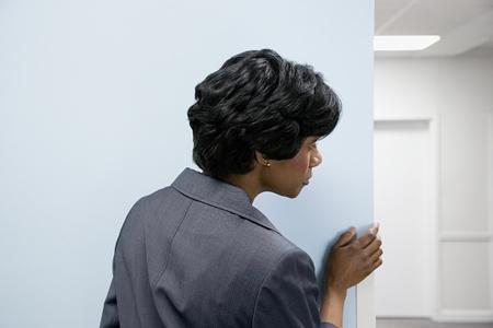 empleado de oficina: Ocultaci�n de la mujer mirando la esquina redonda Foto de archivo