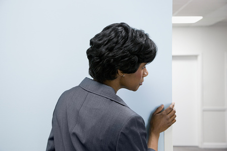 office politics: Woman hiding peering round corner