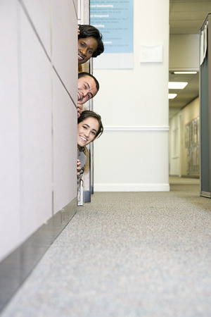 Colleagues peering around cubicle