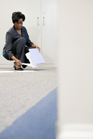 picking up: Businesswoman picking up paper Stock Photo