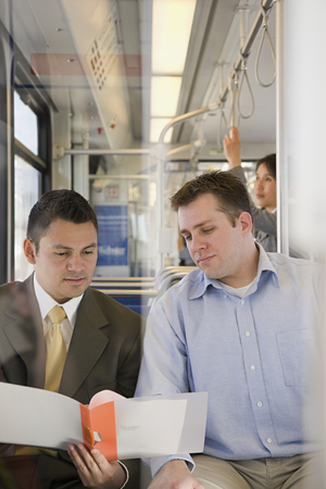 korean ethnicity: Men looking at file on train