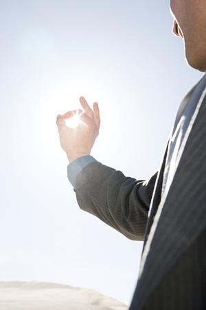 desierto: Hombre con los dedos alrededor de la luz del sol