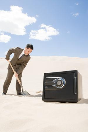 Man digging by safe in desert Reklamní fotografie