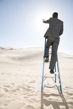 religious clothing: Man on ladder in the desert