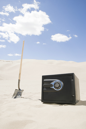 Safe and spade in desert Stock Photo
