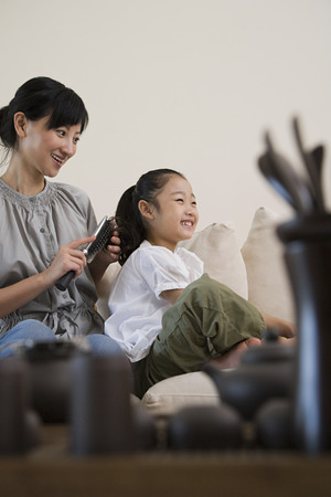 one room school house: Mother brushing her daughters hair
