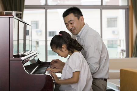 Father and daughter playing the piano