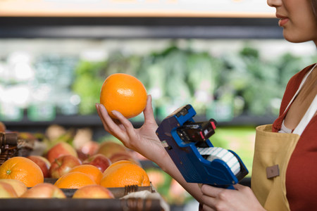 grocery shelves: sales assistant pricing an orange Stock Photo