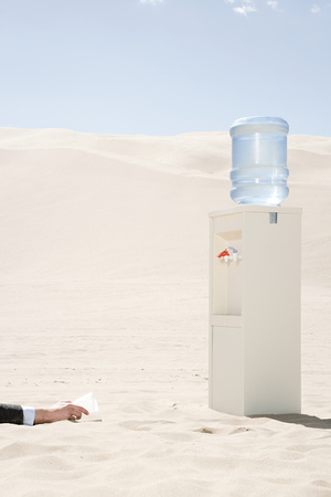 water cooler: Person reaching for water cooler in desert