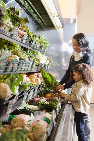 comidas saludables: madre entrega a su hija acelgas Foto de archivo