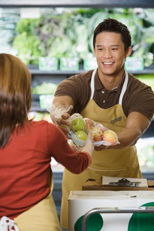 Sales assistants handing packets of apples Standard-Bild