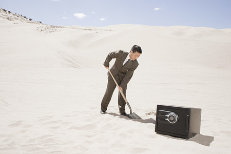 Man digging by safe in desert Stock Photo