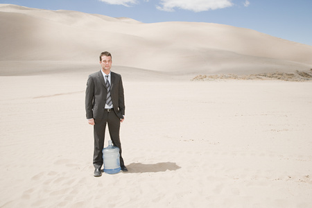thirst: Man in desert with water bottle Stock Photo