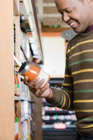 checking ingredients: man holding a jar Stock Photo