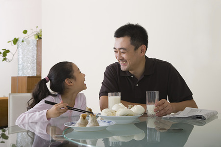family with one child: Father and daughter sat at a table
