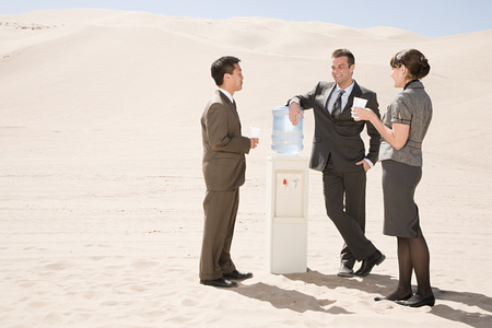asian man: People around water cooler in the desert