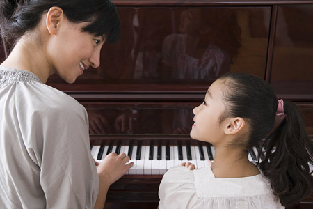 piano lesson: Mother and daughter playing the piano