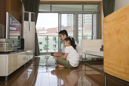 family with one child: Father and daughter playing a video game