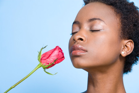 smelling: Woman smelling rose Stock Photo