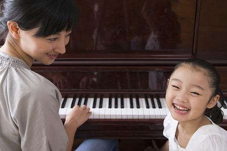 어머니는 그녀의 딸의 피아노 연주