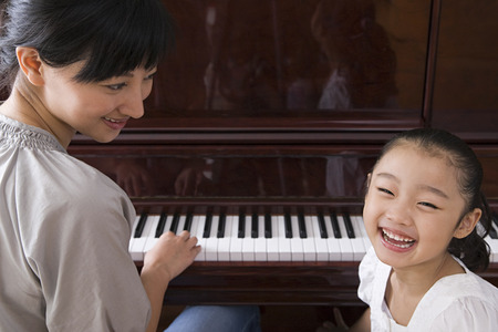 Mother playing the piano for her daughter