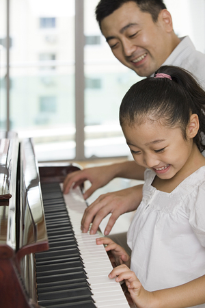 piano lesson: Father and daughter playing the piano