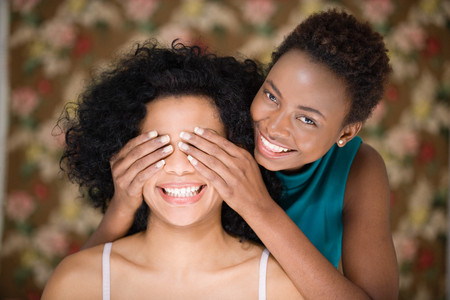two woman: Woman covering friends eyes Stock Photo