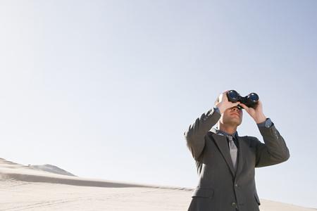 oversee: Businessman in desert with binoculars