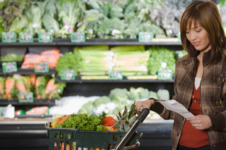 fresh vegetable: young woman holding a shopping list