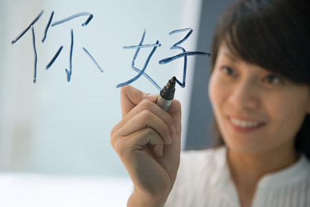 working office: Woman writing hello in Chinese Stock Photo