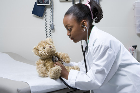 niños enfermos: Médico de niña que usa el estetoscopio en oso de peluche Foto de archivo