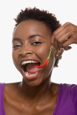 chilli pepper: Woman eating chilli pepper