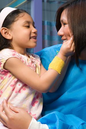 chinese american ethnicity: Nurse holding happy girl