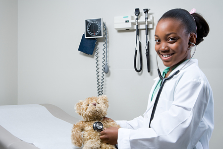 medical occupation: Girl doctor using stethoscope on teddy bear