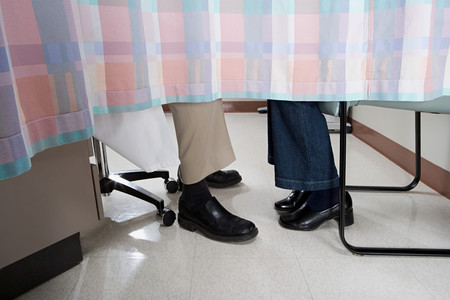 confidentiality: Doctor and patient behind curtain Stock Photo