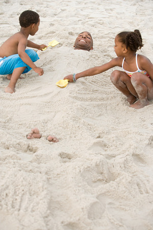 girl in shorts: Children burying father in sand