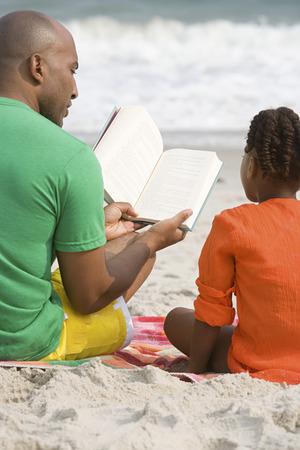 negras africanas: Padre e hija que leen un libro Foto de archivo