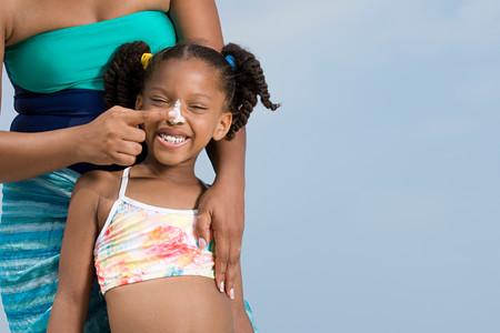 suncream: Mother applying suncream to daughters nose Stock Photo