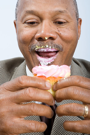 image source: Businessman eating a cupcake Stock Photo