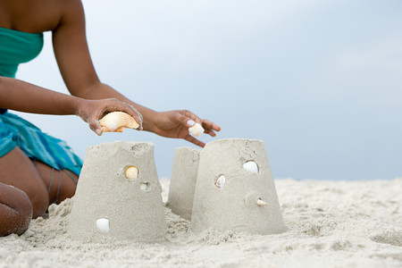female children: Mother and child putting shells on sandcastles