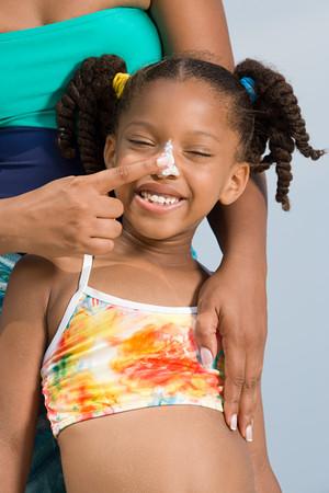 suncream: Mother putting suncream on daughters nose Stock Photo