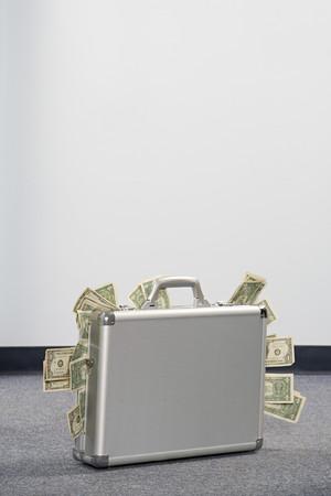 Money in a briefcase Imagens