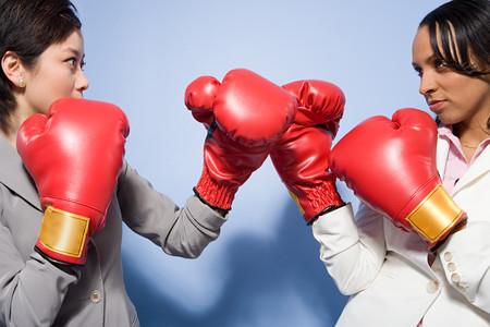 Two businesswomen boxing