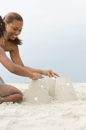 sandcastles: Mother and daughter making sandcastles Stock Photo