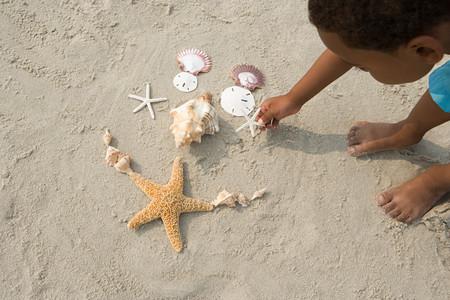 garcon africain: Boy fabrication de modèles avec des coquillages