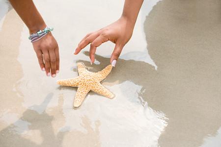 ni�os vistiendose: Madre e hija recogiendo estrellas de mar