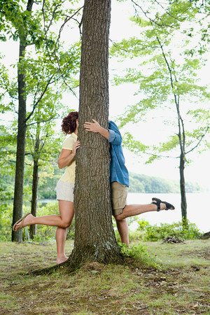 concealment: Couple kissing behind a tree