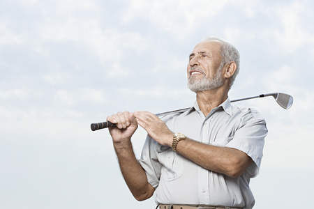 man looking out: Man holding a golf club Stock Photo